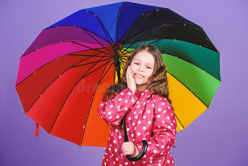 Enjoy rain concept. Kid girl happy hold colorful rainbow umbrella. Rainy weather with proper garments. Bright umbrella stock image