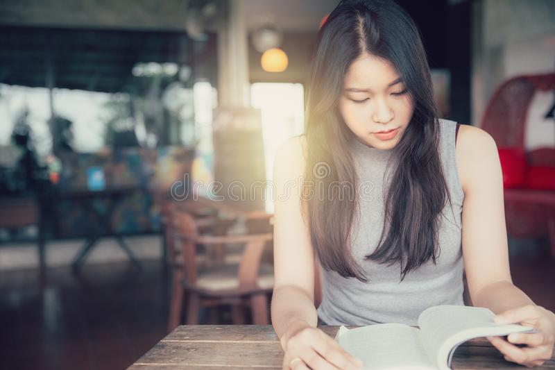 Enjoy relax times with reading book, Asian women Thai teen smile with book in coffee shop stock image