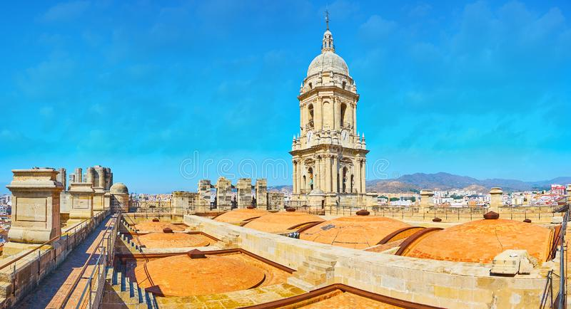Panorama with bell tower of Malaga Cathedral, Spain. Enjoy the rooftop walk on Malaga Cathedral with a view on its domes and tall stone bell tower, Andalusia royalty free stock images