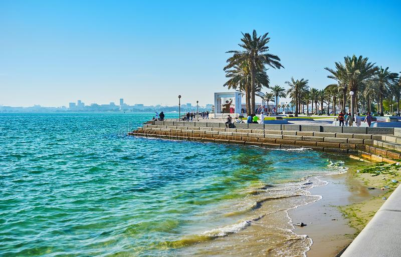 Enjoy the seascape in Doha, Qatar. DOHA, QATAR - FEBRUARY 13, 2018: The scenic seascape from the corniche promenade with a view on green palms and gentle waves royalty free stock images