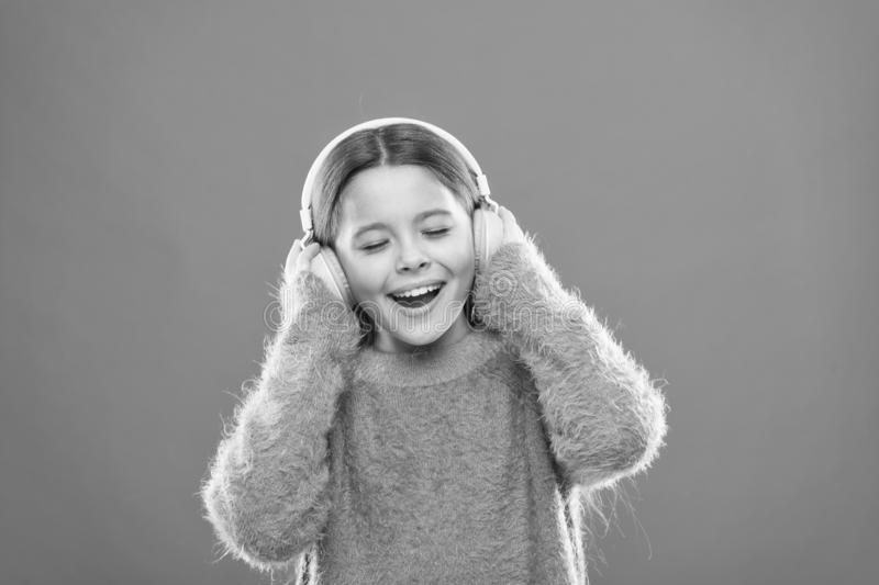 Enjoy sound. Girl cute little child wear headphones listen music. Kid listen music orange background. Recommended music royalty free stock photos