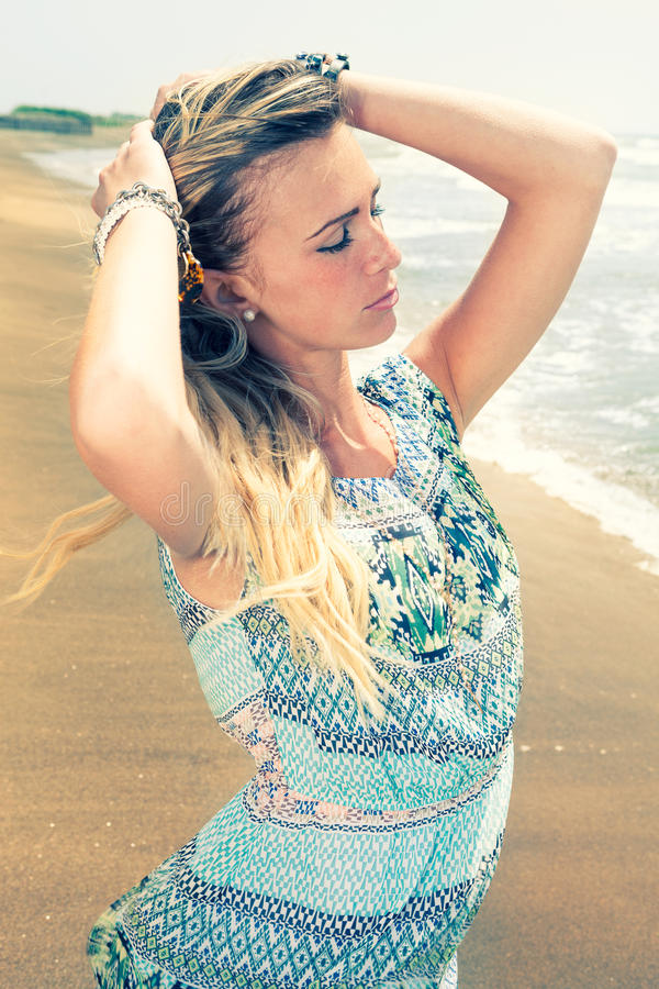 Enjoy the summer. Young beautiful woman at the sea. A blonde girl with hands in her hair is breathing the sea air. She is relaxed with her eyes closed. She royalty free stock images