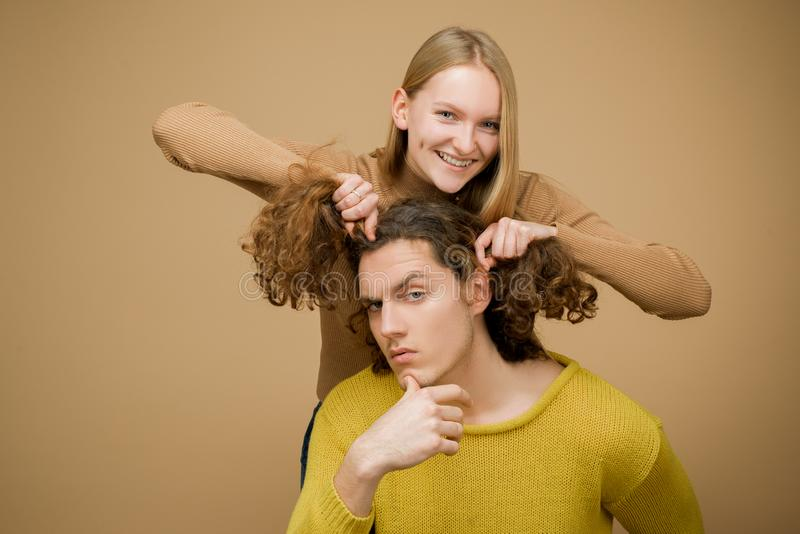 Enjoy twogether. A blonde girlfriend making funny hairstyle to her boyfriend with curly hair. Young couple doing a joke royalty free stock photography