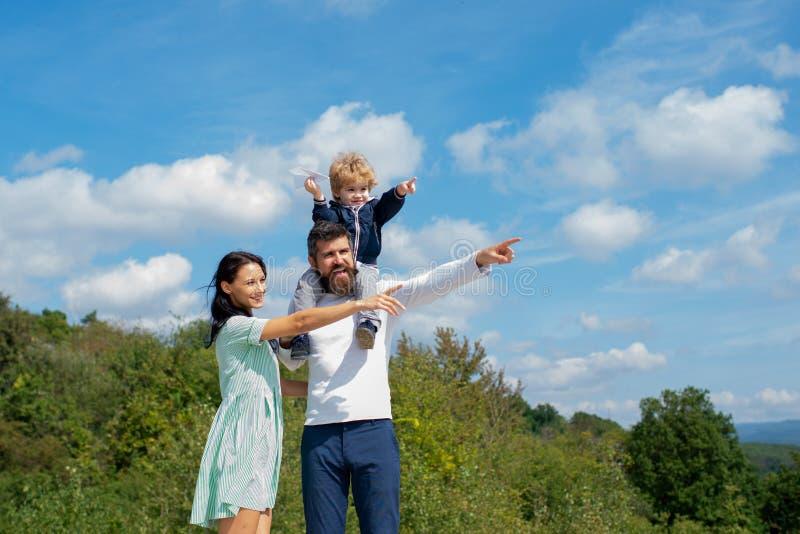 enjoy Vater, der Sohnfahrt auf Rückseiten- und Umarmungsfrau im Park gibt Lustige Zeit lizenzfreie stockfotos