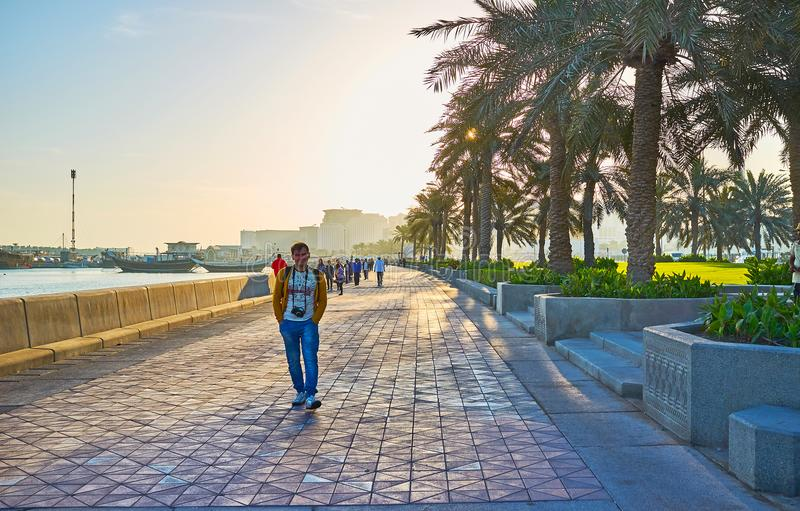 Enjoy the walk in Doha, Qatar. DOHA, QATAR - FEBRUARY 13, 2018: The morning in Corniche promenade with a view on walking people and dhow boats in Doha harbor, on stock photos