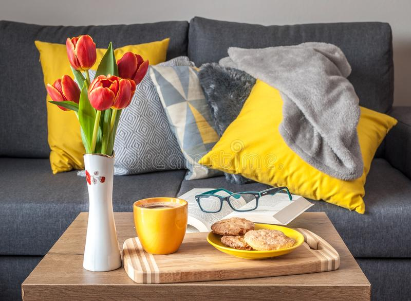 Enjoy Your Free Time with a Cup of Coffee, a Sweet Cookie and Your Favorite book. Scandinavian style sofa with pillows royalty free stock photo