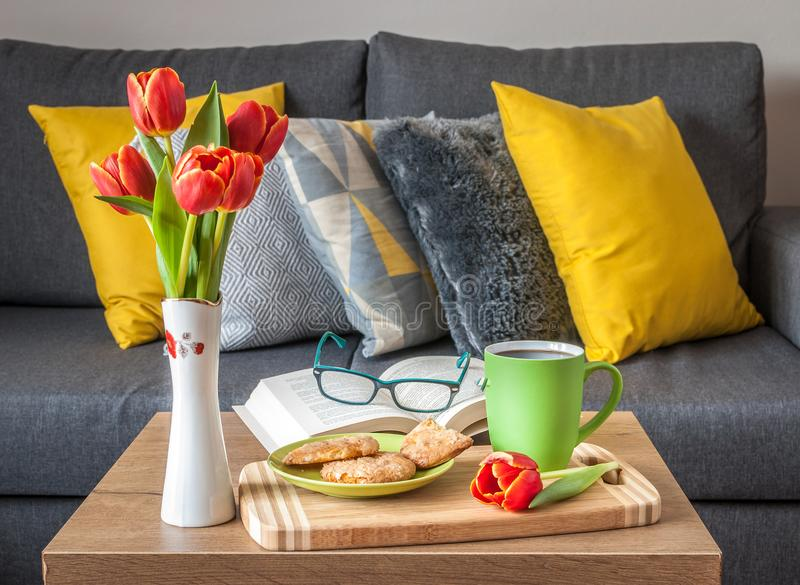 Enjoy Your Free Time with a Cup of Coffee, a Sweet Cookie and Your Favorite book. Scandinavian style sofa with pillows stock photos