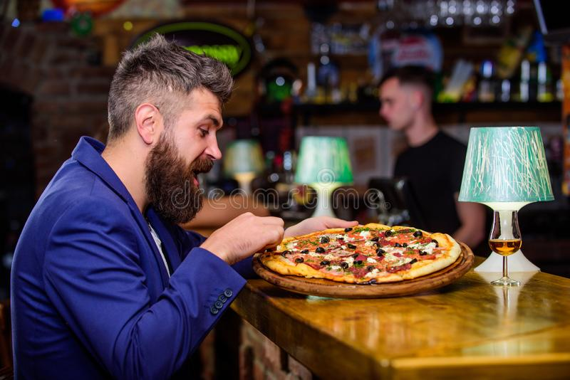 Enjoy your meal. Cheat meal concept. Hipster hungry eat italian pizza. Pizza favorite restaurant food. Fresh hot pizza. For dinner. Hipster client sit at bar royalty free stock photo