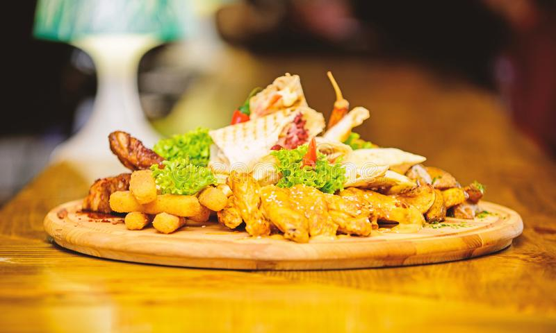 Enjoy your meal. Pub menu snack. Meat snack for group friends. Tasty delicious snacks. Snack for beer. Restaurant food. Wooden board french fries fish sticks stock photo