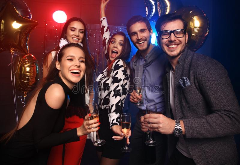 Enjoying amazing party. Group of beautiful young people dancing with champagne flutes and looking happy. New year`s party stock photography