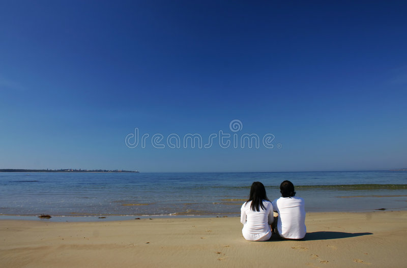Enjoying beach. Couple looking at the sea royalty free stock images