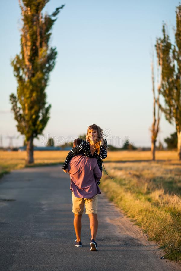 Enjoying beautiful day. Rear view of young cheerful man carrying his beautiful girlfriend on shoulder royalty free stock photo