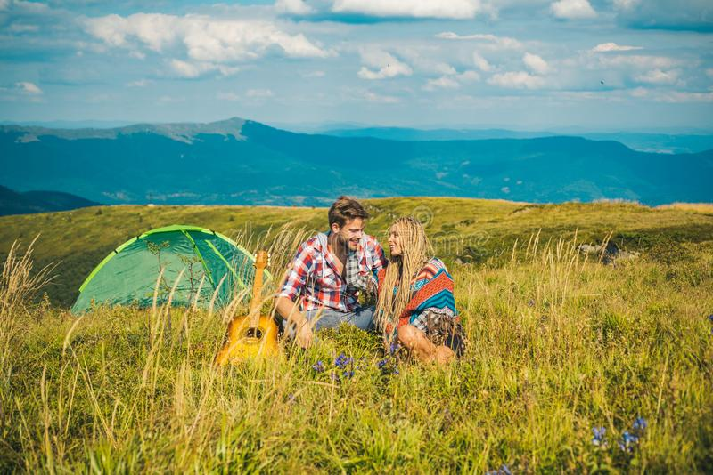 Enjoying the beautiful landscape of couples camping in the mountains. Happy couple tourists man and woman having a rest stock photography