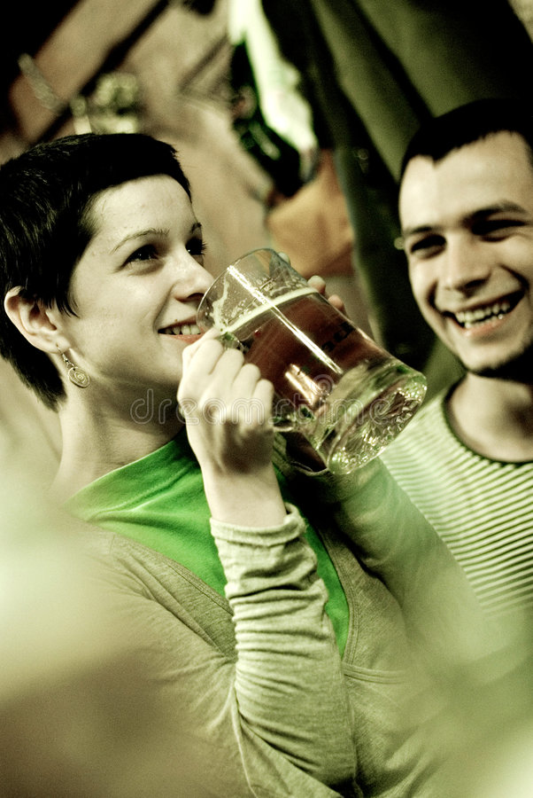 Enjoying beer. Woman enjoying glass of beer while adult male looks on with amusement. Image shows noise royalty free stock images