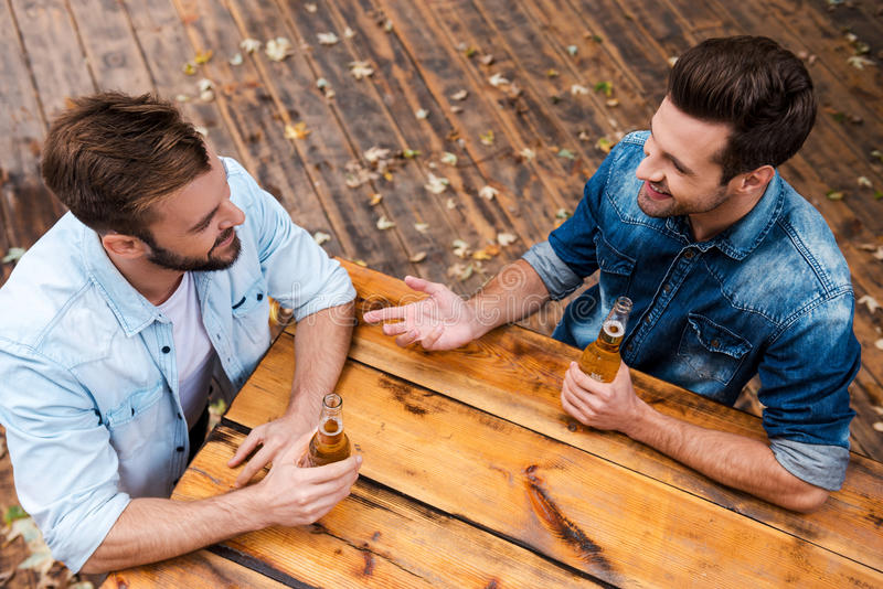 Enjoying beer with friend. Top view of two smiling young men drinking beer and talking to each other while standing outdoors stock photo