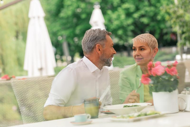 Couple of mature husband and wife enjoying breakfast outside stock photos