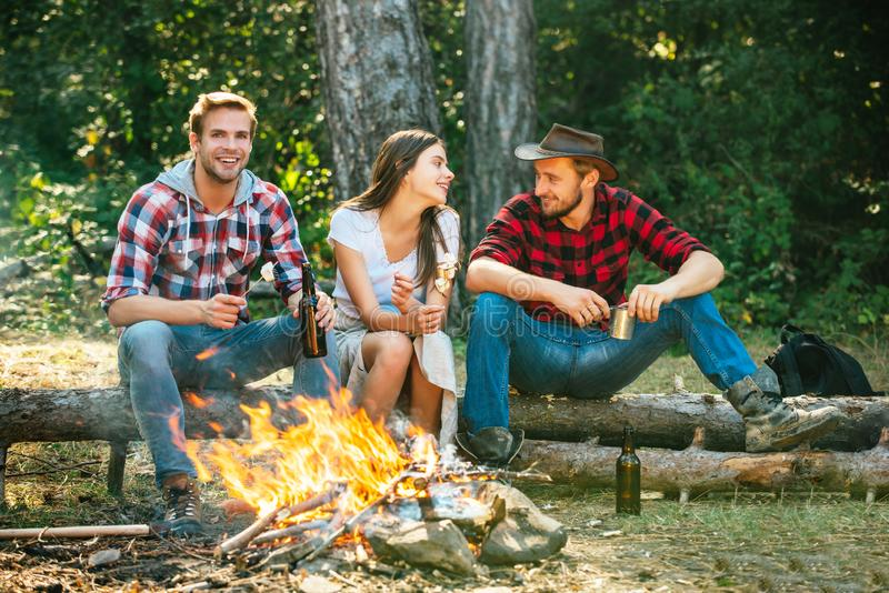 Enjoying camping holiday in countryside. Happy people sitting around campfire. Friends enjoy weekend barbecue in forest stock photography