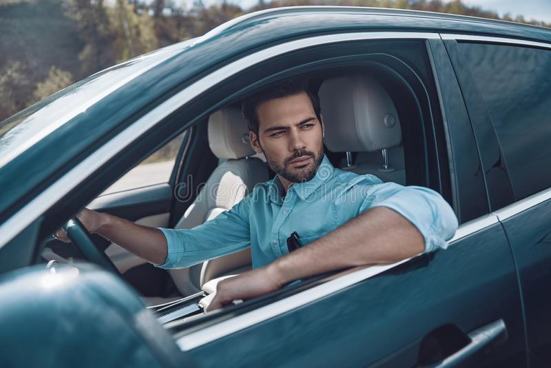 Enjoying car ride. Handsome young man in smart casual wear looking away while driving a status car royalty free stock image