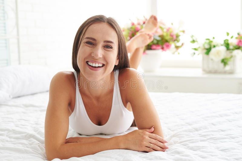 Enjoying a carelessness morning at home. A woman lying on the bed looking forward and smiling while enjoying a carelessness morning at home stock image