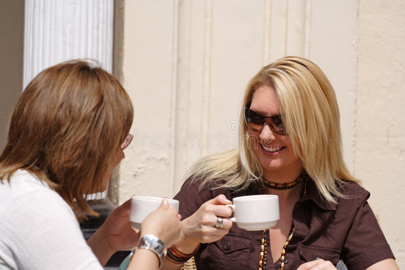 Enjoying coffee alfresco style. Two ladies taking coffee and lunch at an outside restaurant stock photo