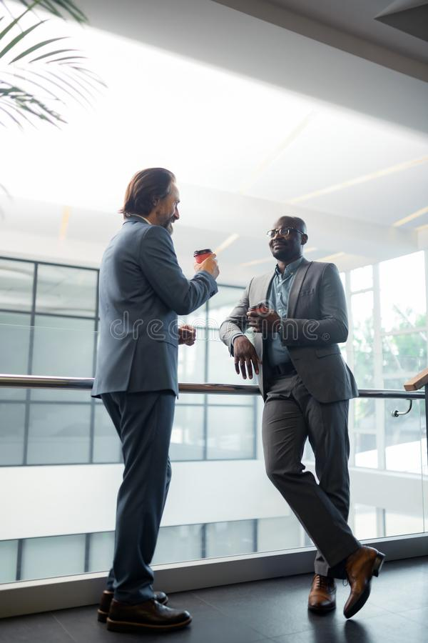 Businessmen feeling rested while enjoying coffee break in the office stock photos