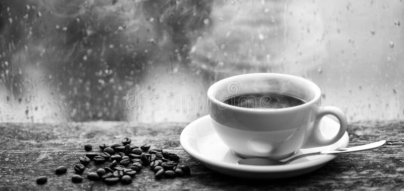Enjoying coffee on rainy day. Coffee morning ritual. Fresh brewed coffee white mug and beans on windowsill. Wet glass stock image