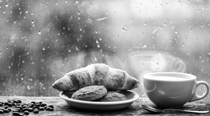 Enjoying coffee on rainy day. Coffee time on rainy day. Fresh brewed coffee in white cup or mug on windowsill. Wet glass royalty free stock photography