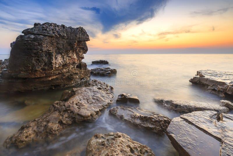 Enjoying the colorful sunset on a beach with rocks on the Adriatic Sea coast Istria Croatia stock photos