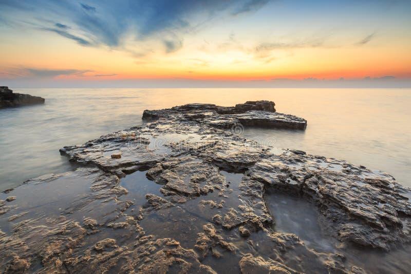 Enjoying the colorful sunset on a beach with rocks on the Adriatic Sea coast Istria Croatia royalty free stock photos