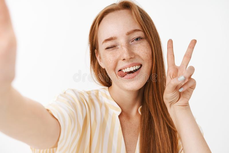 Enjoying cool summer holidays. Stylish beautiful redhead woman with cute freckles sticking out tongue and grinning from stock photography