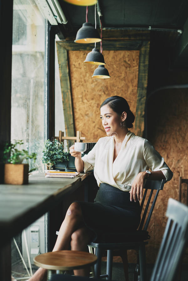 Enjoying cup of coffee. Attractive Vietnamese business woman drinking coffee and looking through cafe window stock photography