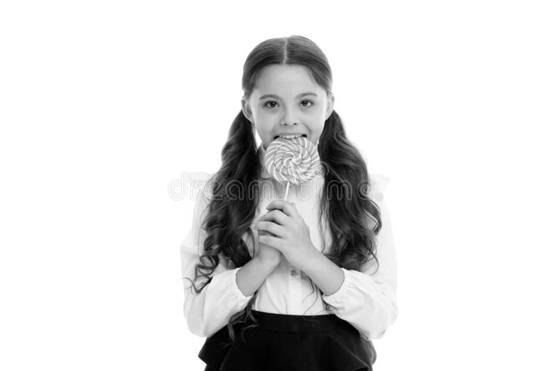 Enjoying delicious candy. Girl cute kid ponytails hairstyle eats sweet lollipop. Sweets in appropriate portions ok. Girl. Pupil school uniform likes sweets stock photos