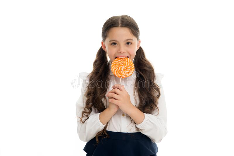Enjoying delicious candy. Girl cute kid ponytails hairstyle eats sweet lollipop. Sweets in appropriate portions ok. Girl. Pupil school uniform likes sweets royalty free stock image
