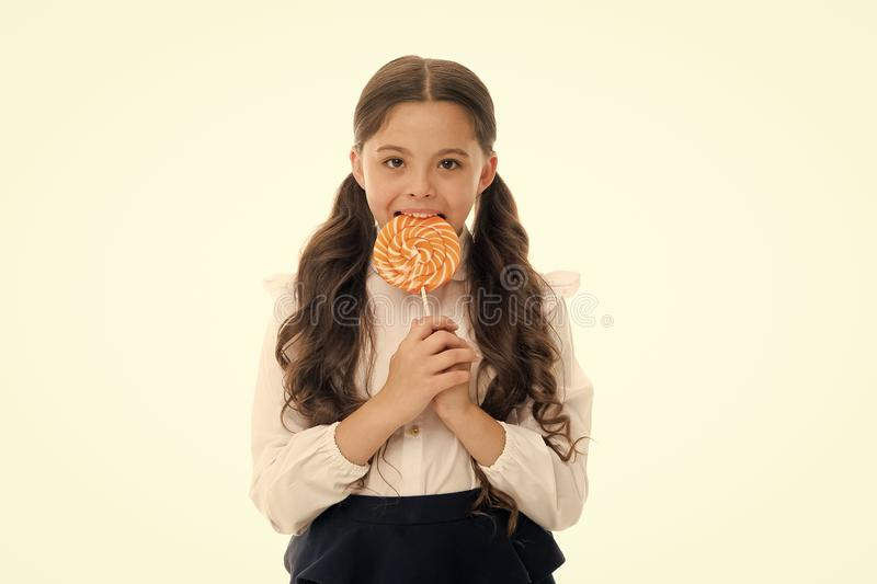 Enjoying delicious candy. Girl cute kid ponytails hairstyle eats sweet lollipop. Sweets in appropriate portions ok. Girl. Pupil school uniform likes sweets stock photo