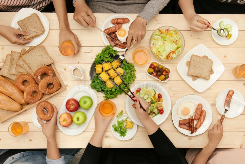 Enjoying dinner with friends. Top view of group of people having dinner together while sitting at wooden table royalty free stock images
