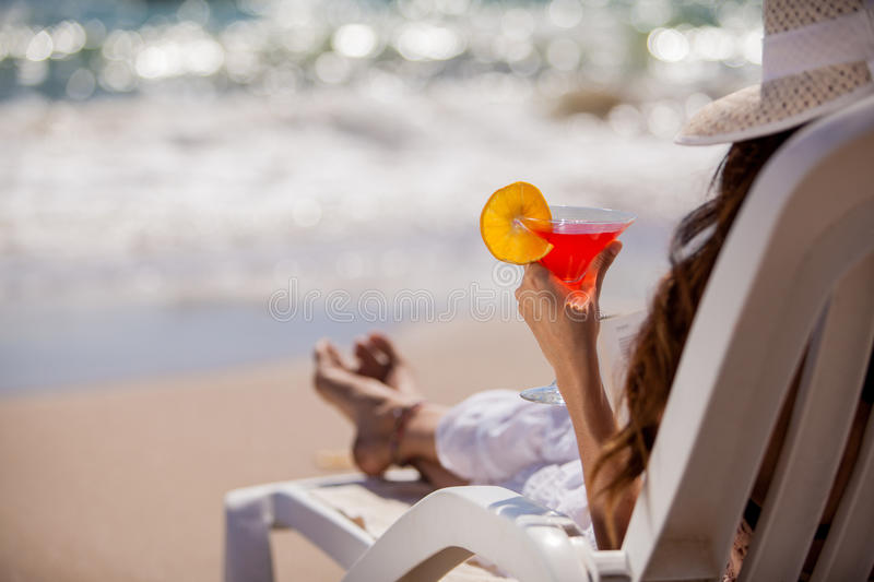 Enjoying a drink by the beach. Closeup of a young woman relaxing at the beach with a cold martini royalty free stock photos
