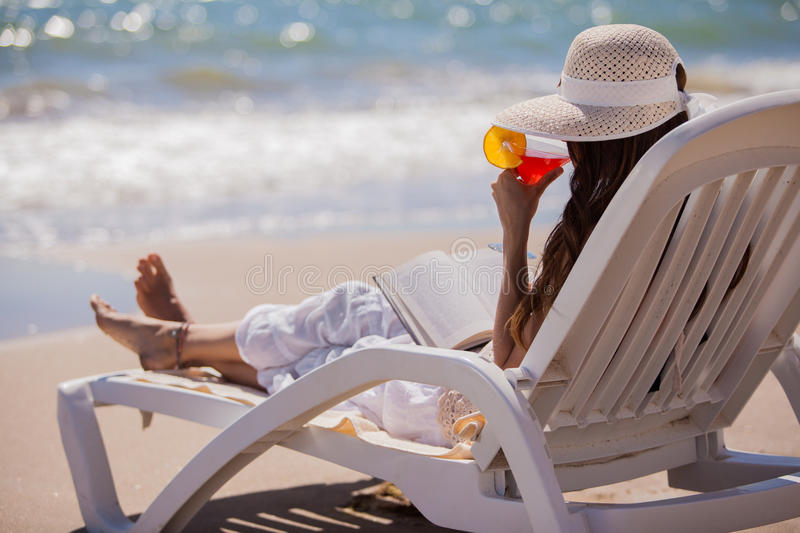 Enjoying a drink by the beach. Young woman relaxing at the beach while reading a book and drinking martinis royalty free stock image