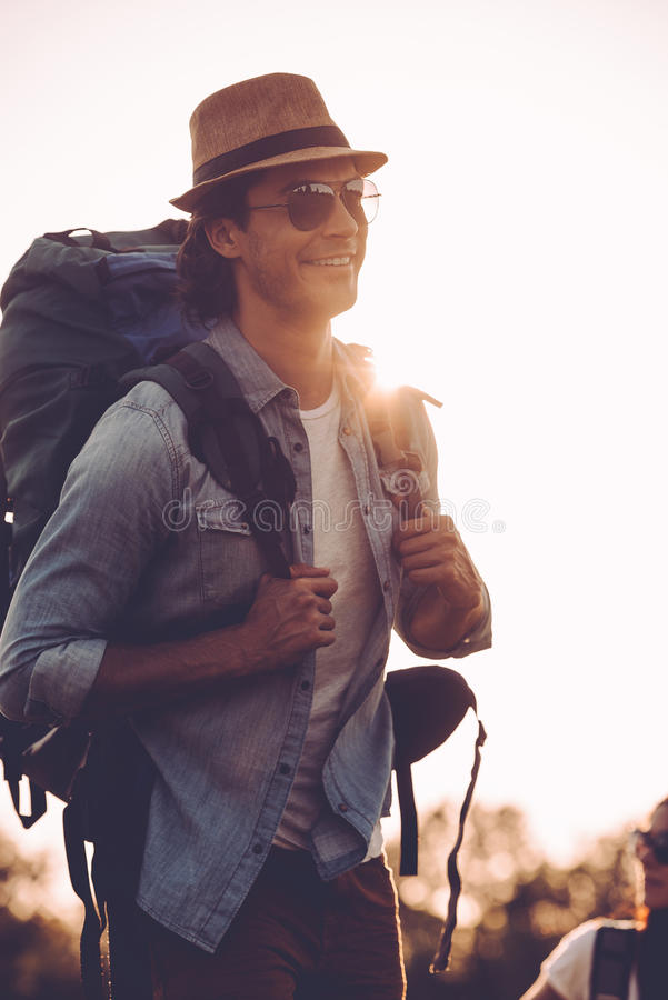 Enjoying early morning hike. Handsome young man in fedora carrying backpack and smiling while walking outdoors stock images