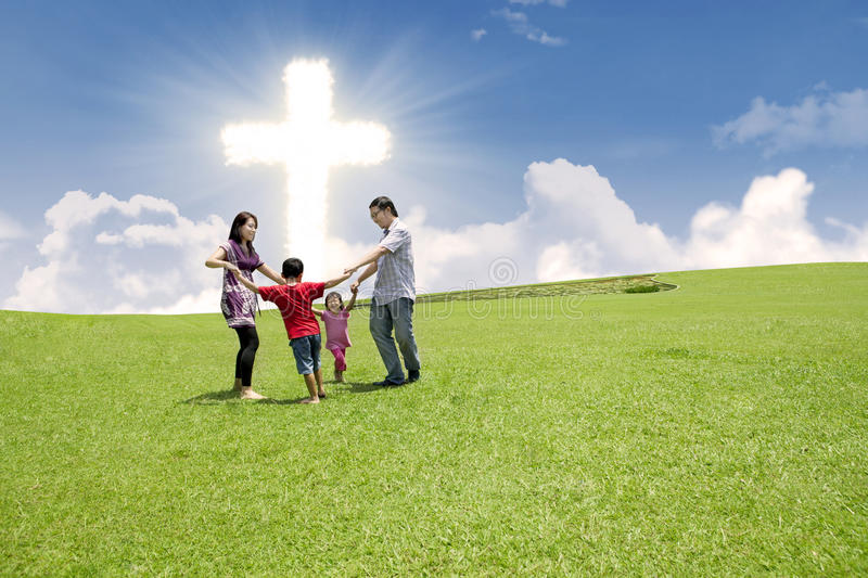 Enjoying Easter holiday together. Christian family enjoying their Easter holiday in the park under bright Cross sign stock images