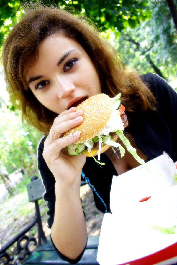 Enjoying eating Fast food. Young girl enjoying eating fast food hamburger royalty free stock images
