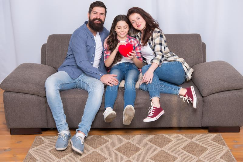 Enjoying every moment together. bearded man and woman with child hold red heart. happy family at home on weekend. mother stock images