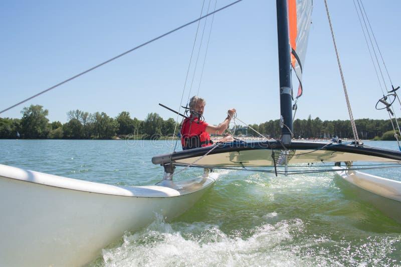 Enjoying extreme sailing with racing sailboat stock photography