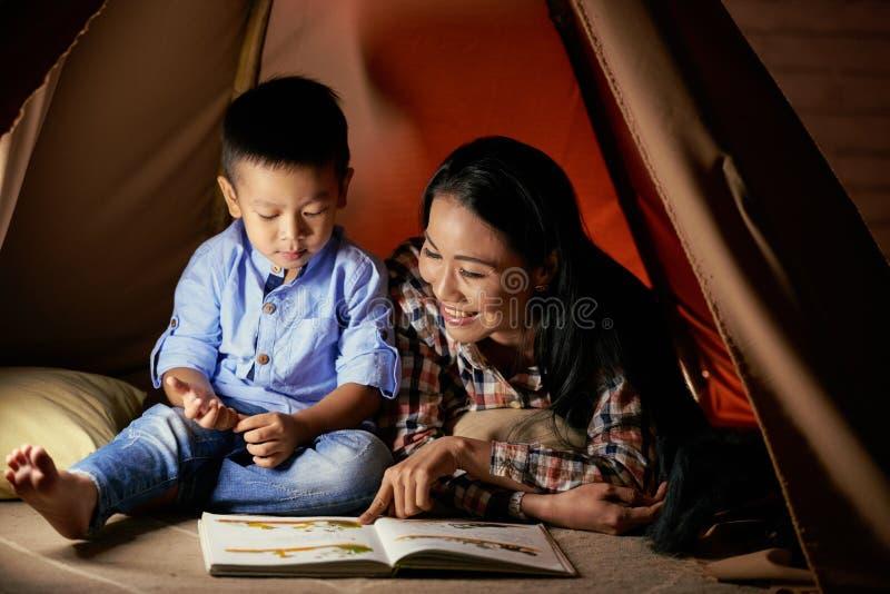 Enjoying fairytale. Cute Asian little boy listening to his mother reading fairytale stock photo