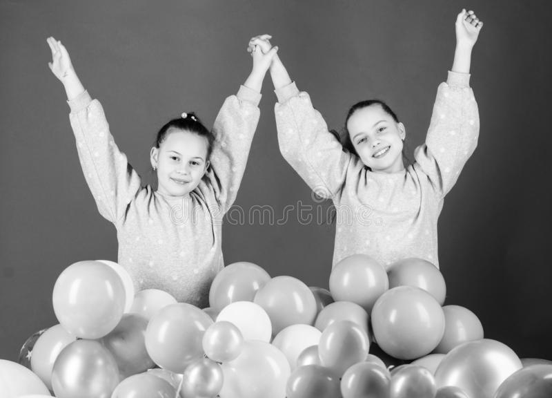 Enjoying family holiday together. Happy little girls having holiday celebration. Happy holiday. Celebrating birthday. Air balloons creating a real holiday for stock images