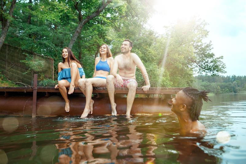 Enjoying river party with friends. Group of beautiful happy young people at the river together stock photography