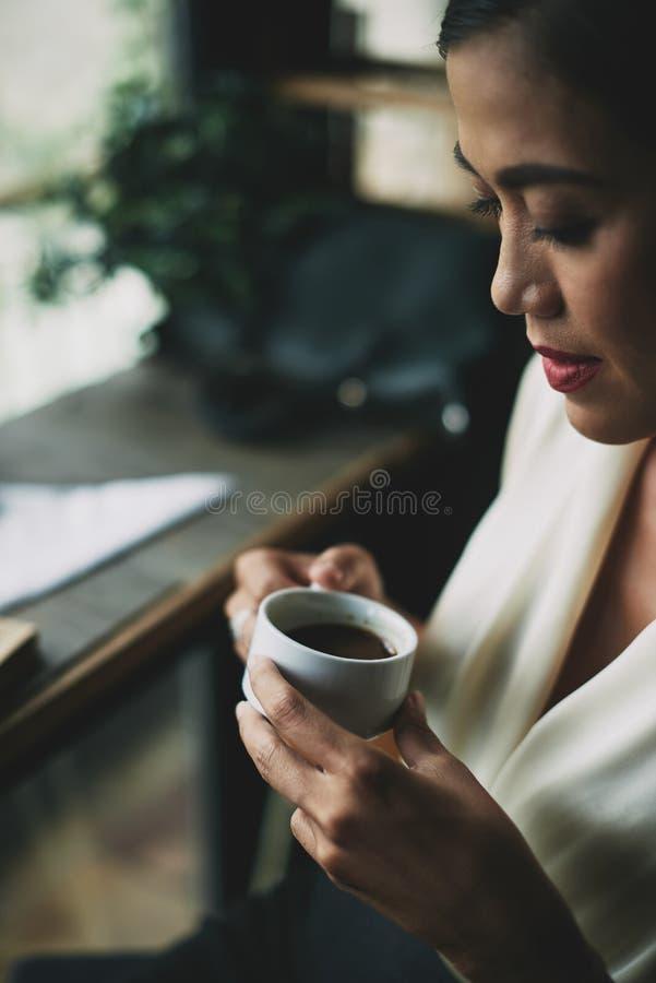 Enjoying fresh espresso. Close-up image of woman enjoying cup of espresso stock images