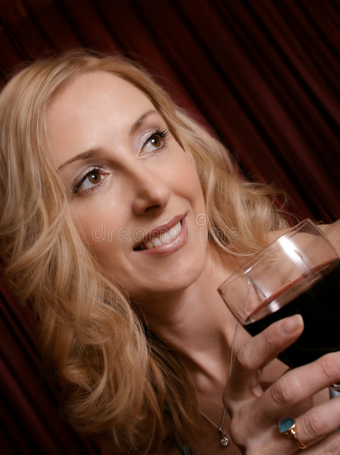 Enjoying a glass of red. Female enjoys a glass of red (angled closeup royalty free stock photos