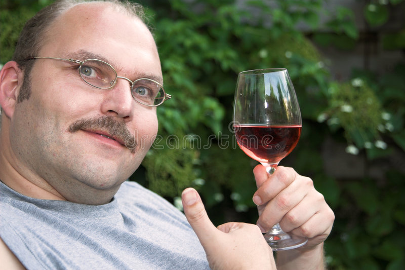 Enjoying a glass of wine. Handsome mature man enjoying a glass of rose in the garden royalty free stock images