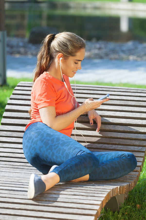 Enjoying good music. Young sporty girl having rest and enjoying good music royalty free stock images