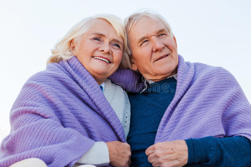 Enjoying a great day together. Low angle view of happy senior couple bonding to each other and smiling while being covered with plaid royalty free stock photos